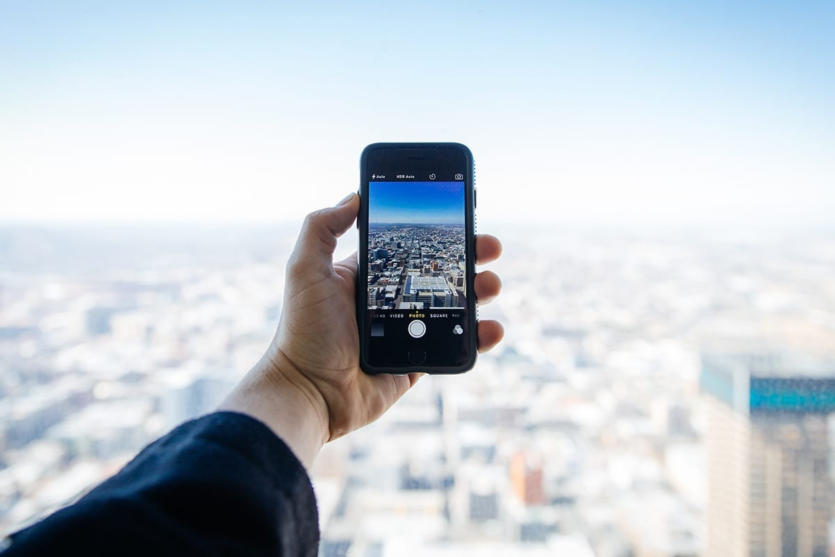 person takes a picture with a phone of a city