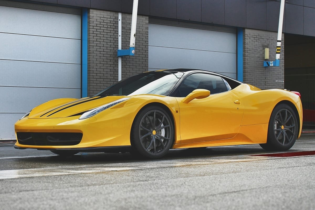 Yellow Ferrari car in front of a garage | before clipping path service