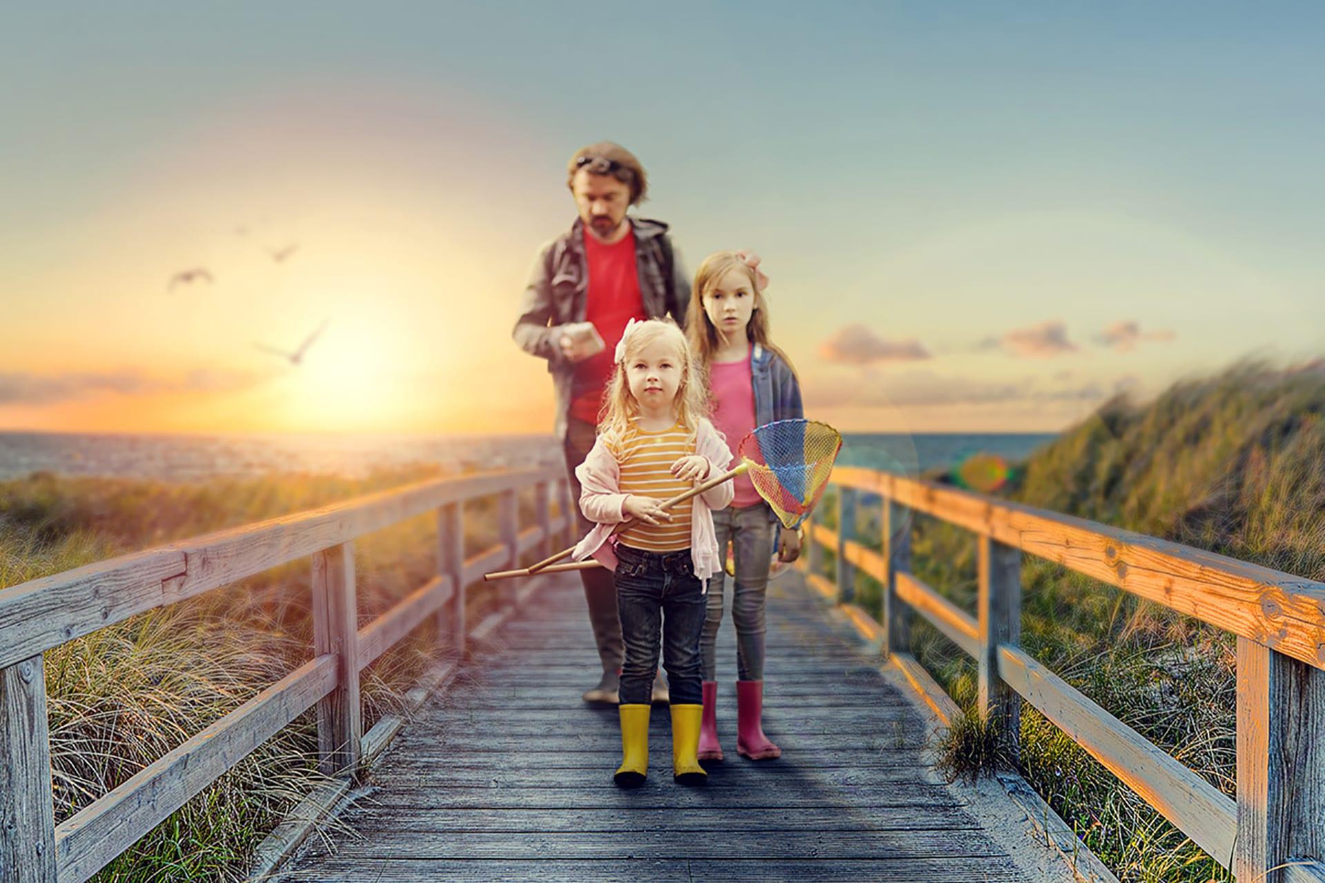Familie steht auf einer Holzbrücke vor einem Sonnenuntergang | nach der Retusche