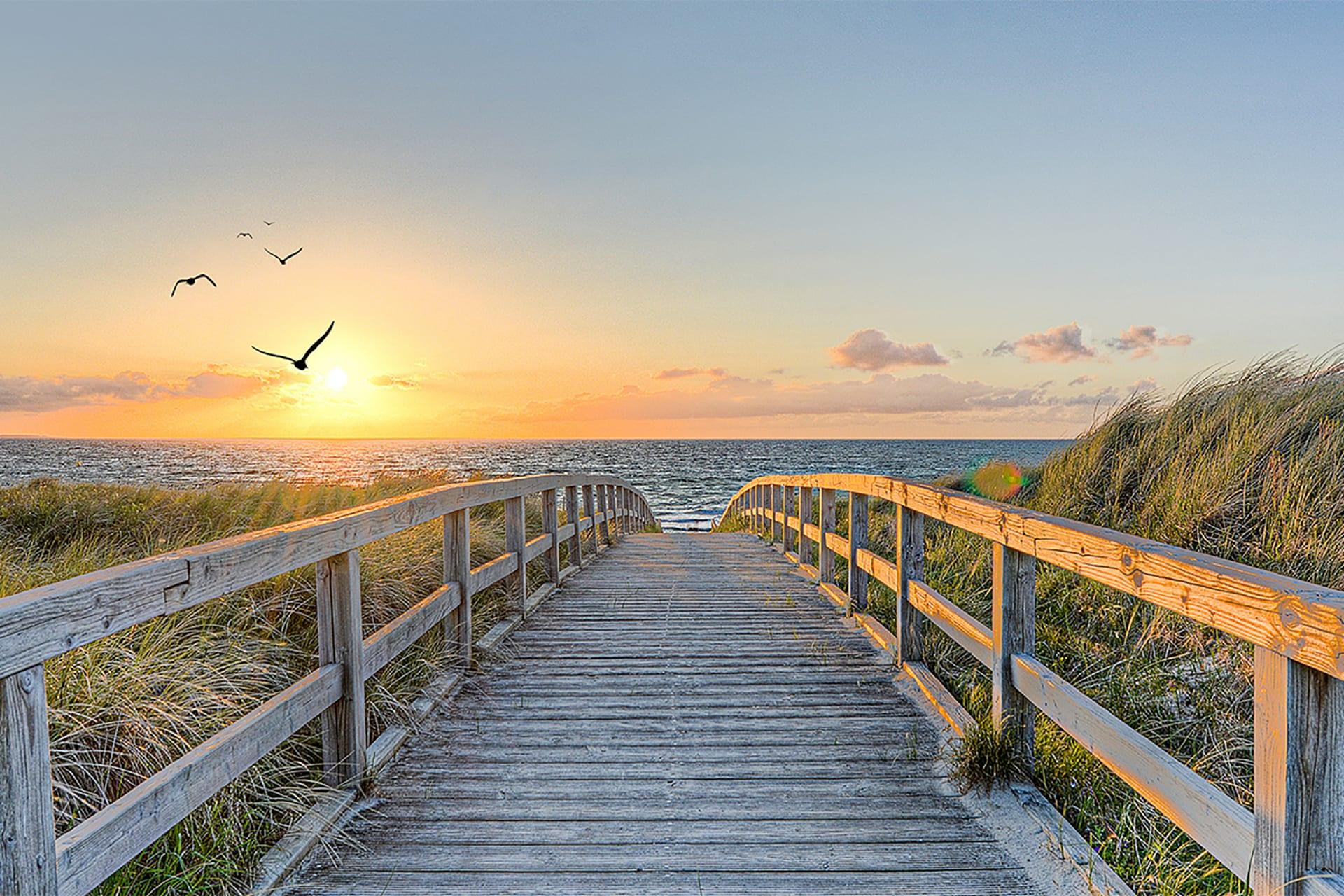Holzbrücke die zum Meer führt. Sonnenuntergang im Hintergrund | vor der Retusche