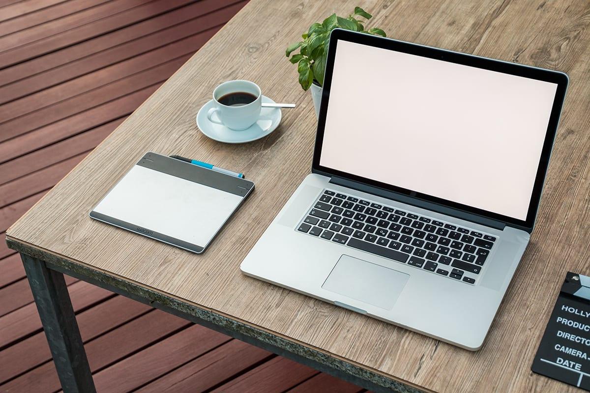 Ein offener laptop auf einem Holztisch mit einem Grafiktablet daneben | ohne Freisteller Service