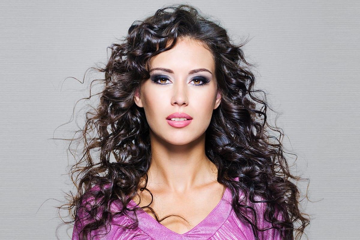 Weibliches Modell mit welligen Haaren auf grauem Hintergrund | vor Softclipping