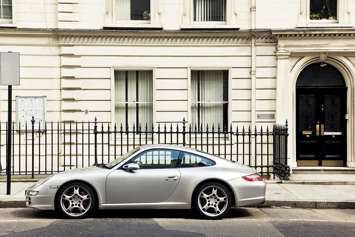 Porsche steht auf einer dreckigen Straße vor einem Metallzaun und einem beigen Haus | vor der Retusche