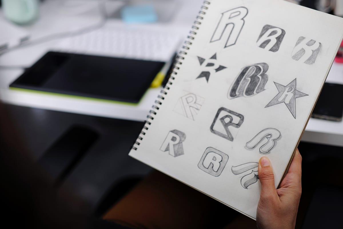 eine Person hält ein Notizbuch mit vielen logo scribbles